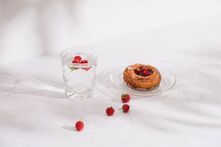 Sweet summer dessert, homemade puff pastry with berries , served with cold raspberry cider, fresh raspberries. On a white marble table, copy space top view
