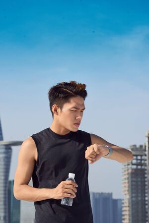 Young male athlete checking smartwatch, over shoulder view 写真素材