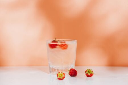 Summer juice with fresh raspberries in a glass on a light background