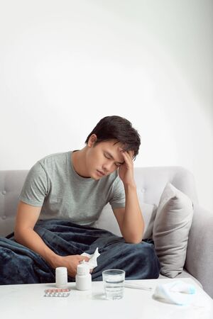 man with headache having in front warm water glass and pills