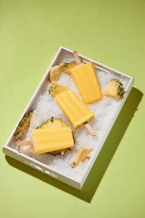 Yellow fruit popsicles on a tray top view, summer mood Stockfoto