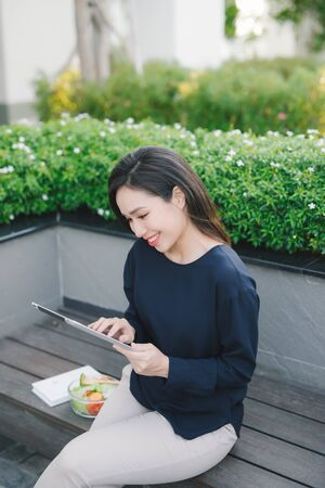 A young cute girl sitting in the park working scrolling a tablet Reklamní fotografie - 124815942