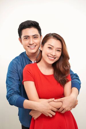 Portrait of a young couple hugging and standing against white background