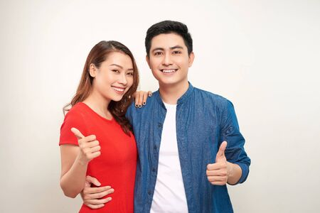 Young couple over isolated background smiling with happy face looking and pointing to the side with thumb up