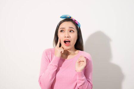 Giovane bella donna asiatica spaventata dal sole isolato su sfondo bianco. Concetto per la cura della pelle estiva e la protezione della pelle dai raggi UV