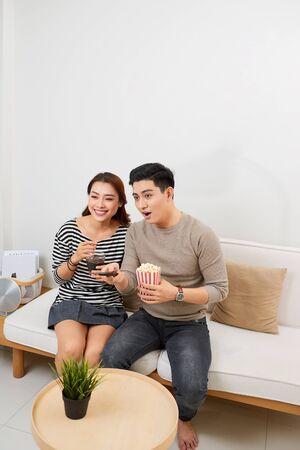 Feliz pareja joven tumbado en el sofá en casa con palomitas de maíz viendo la televisión Foto de archivo