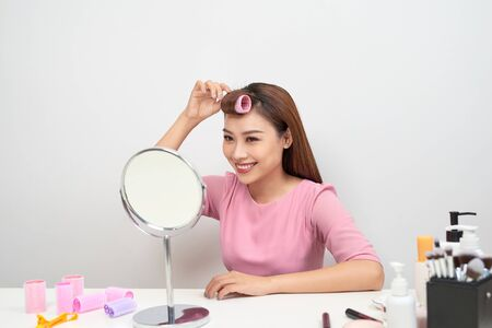 Beautiful woman with curlers smiling into mirror, enjoying her look, beauty Zdjęcie Seryjne