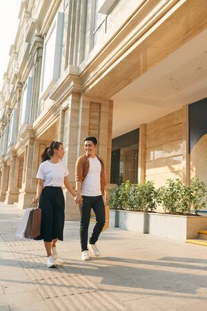 Beautiful young diverse tourist couple holding hands walking through streets in city,