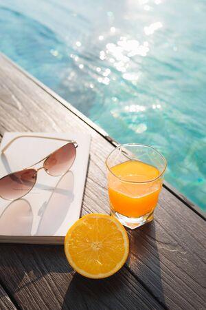 Orange fresh juice, book and sunglasses near pool