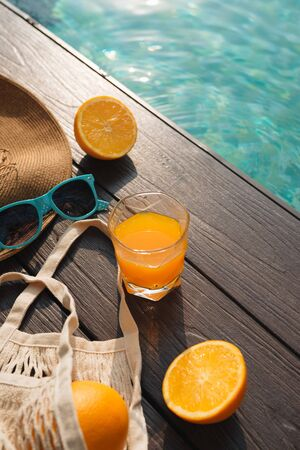 Beach hat, orange juice and sunglasses near the swimming pool