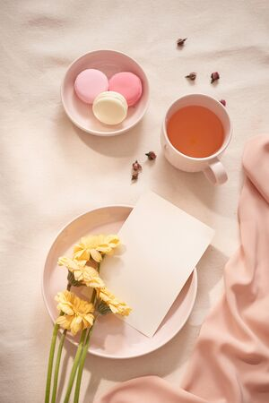 Tea cup with Rose tea and fresh  flower and macarons on white background