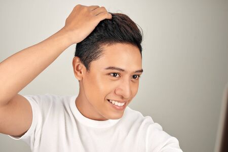 Happy handsome smiling Asian man touching his hair Standard-Bild