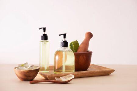 Bolw of aloe on cutting board and organic shower gel in bottle on wood tray