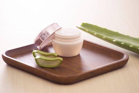 Aloe vera cosmetic cream on wooden tray with aloe leave on light background. Foto de archivo - 125426659