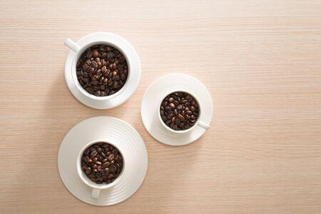 Volle Kaffeebohnenbecher auf dem Holzhintergrund