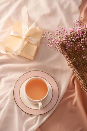 Cup of tea, gift box and flowers on light background Stock Photo