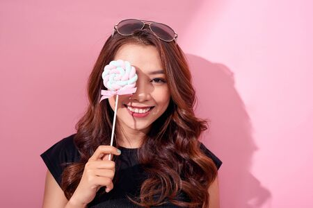 Funny girl covered eye with lollipop and laughing over pink background