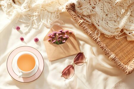 Flowers in envelope with glasses and cup of tea on fabric background