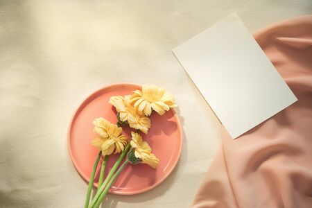 Flowers on the plate with fabric and card on yellow background