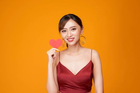 happy young woman dressed in red dress holding paper heart isolated over yellow background 写真素材