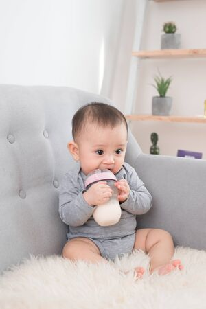 Little cute baby girl sitting in room on sofa drinking milk from bottle and smiling. Happy infant. Family people indoor Interior concepts. Childhood best time!