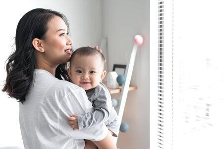 Beautiful young mom is playing with her cute baby and smiling while standing near the window at home 스톡 콘텐츠 - 125685517