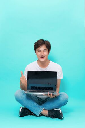 Modern lifestyle and people concept. Handsome asian male student sitting on floor with crossed legs, holding notebook and smiling at camera over blue background. Intilligent designer creating ideas