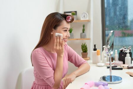 Cosmetic beauty procedures and makeover concept. Woman in hair curlers beautiful young woman using cotton pads at home Standard-Bild - 125685521
