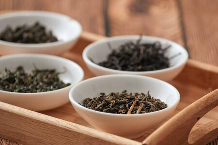 the white drinking bowls of assortment of dry tea in order on wooden background
