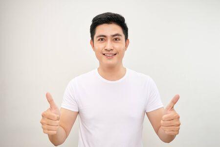 junger asiatischer mann, der zwei daumen hoch zeigt Standard-Bild