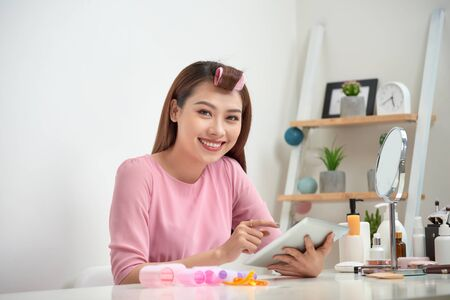 Happy asian woman wearing hair curlers using tablet at home