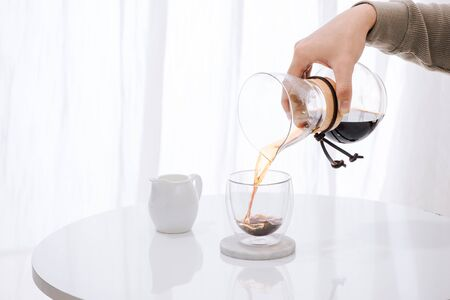 Brewing nel drip coffee. Step by step cooking instructions. Coffee is ready. Barista pouring brewed coffee in the cup Foto de archivo - 127064974