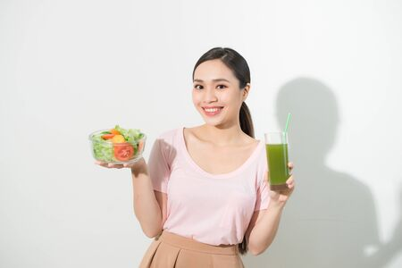 Woman with green detox smoothies, salad in glass bowl isolated on white background. Proper nutrition, vegetarian food, healthy lifestyle, dieting concept. Area to copy space