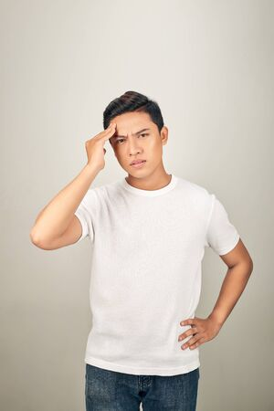 Good-looking asian man showing how much his head hurts, experiencing pain, looking miserable and exhausted