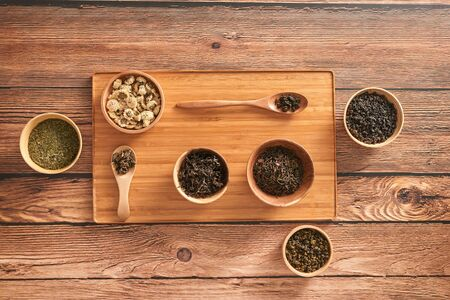 assortment of dry tea in white bowls on wooden surface