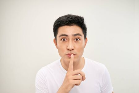 Asian man over isolated white wall showing a sign of silence gesture putting finger in mouth 版權商用圖片