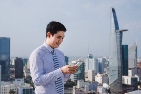 Businessman using mobile phone app texting outside of office in urban city with skyscrapers buildings in the background. Young caucasian man holding smartphone for business work. Stock Photo