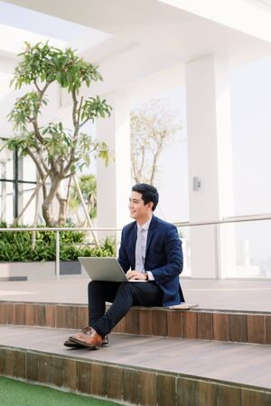Happy young businessman using laptop outside office building Stockfoto