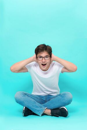 I am so happy you are here. Studio shot of attractive playful asian man, sitting on floor with crossed legs holding hands on head and shouting from excitement and surprise Stock Photo