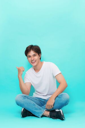 Show me who is in charge. Studio shot of attractive stylish man with trendy glasses sitting with crossed legs on floor smiling friendly and pointing left, posing over blue background. 免版税图像