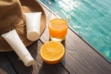 Orange juice, straw hat, sunblock and sunglasses by poolside Imagens