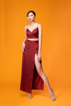 Full length portrait of young sexy woman in red dress  standing and posing against yellow background