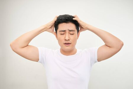 Asian man white shirt feel headache and touch at head by two hand in white background
