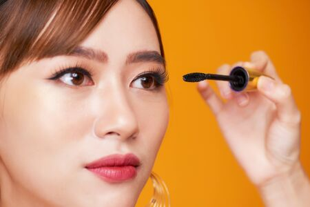 Beautiful woman applying mascara on her eyelashes Imagens