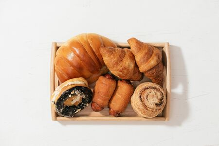 almond donut bun, croissant, crab cake, soft roll cake with sausage put on wooden plate, selective focus