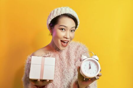 Young woman holding a clock showing nearly 12 Stock Photo