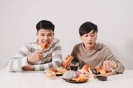 Two friends eating burgers. french fries, having fun and smiling Stock Photo
