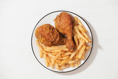 Fried chicken and french fries in white plate isolated on white background
