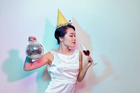 Portrait of a happy beautiful woman in white dress having a party and drinking champagne while standing with disco ball isolated over light background Stockfoto
