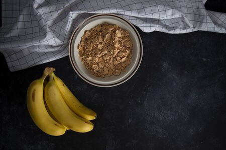 Organic healthy oatmeal porridge with fresh bananas. The white porcelain bowl with napkin 스톡 콘텐츠